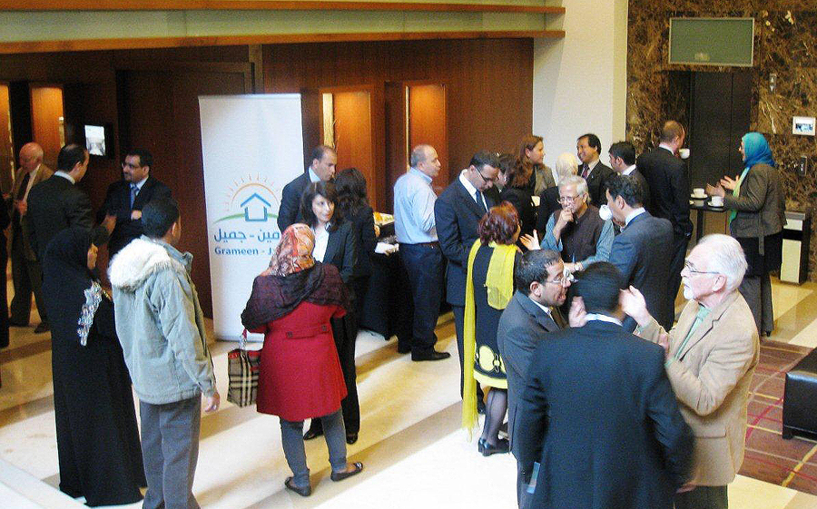 Attendees at the Grameen-Jameel partner meeting mingle during a coffee break.